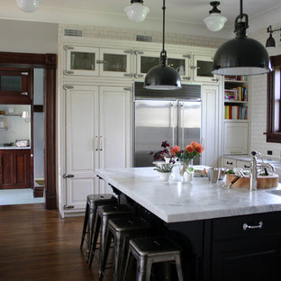 Exemple d'une cuisine chic avec un placard à porte vitrée, une crédence en carrelage métro, un évier de ferme, des portes de placard blanches, une crédence blanche, un électroménager en acier inoxydable et un plan de travail en marbre.