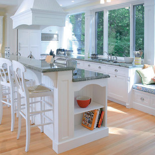 This is an example of a traditional kitchen in Other with panelled appliances, white cabinets and green benchtop.