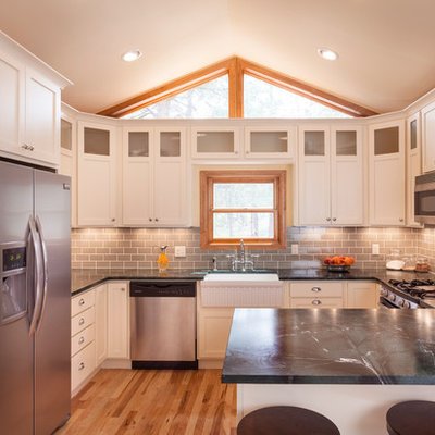 Elegant u-shaped kitchen photo in Denver with glass-front cabinets, stainless steel appliances, subway tile backsplash, a farmhouse sink and soapstone countertops