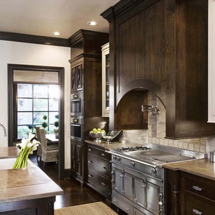 This is an example of a traditional kitchen in Charleston with glass-front cabinets, stainless steel appliances, limestone benchtops, dark wood cabinets, white splashback and subway tile splashback.