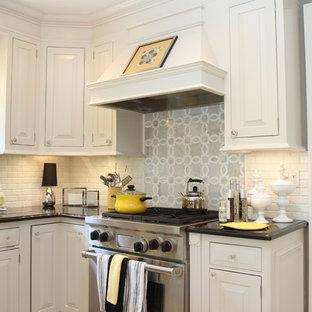 Cette photo montre une cuisine américaine chic en L avec un évier encastré, un placard à porte shaker, des portes de placard blanches, une crédence blanche, un électroménager en acier inoxydable et un plan de travail en béton.