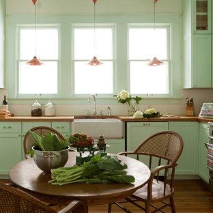 На фото: угловые кухни в классическом стиле с обеденным столом, раковиной в стиле кантри, фасадами в стиле шейкер, зелеными фасадами, деревянной столешницей, бежевым фартуком, техникой из нержавеющей стали и паркетным полом среднего тона без острова