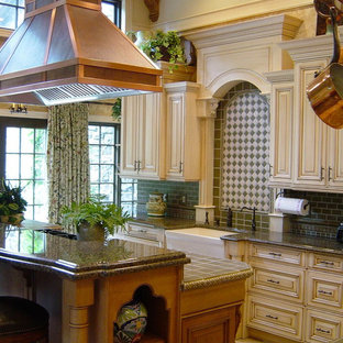 Large traditional enclosed kitchen ideas - Large elegant enclosed kitchen photo in New York with subway tile backsplash, a farmhouse sink, raised-panel cabinets, granite countertops, paneled appliances, beige cabinets and green backsplash