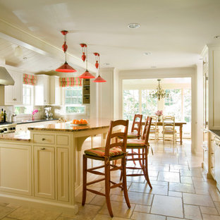 Large traditional eat-in kitchen designs - Example of a large classic u-shaped travertine floor and beige floor eat-in kitchen design in Boston with shaker cabinets, beige cabinets, stainless steel appliances, an island, granite countertops, gray backsplash and ceramic backsplash