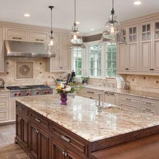 Foto de cocina en L, tradicional, con fregadero bajoencimera, armarios con paneles con relieve, puertas de armario beige, salpicadero beige y salpicadero de piedra caliza