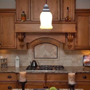 Imagen de cocina clásica con encimera de granito, armarios con paneles empotrados, puertas de armario de madera oscura, salpicadero beige y salpicadero de travertino
