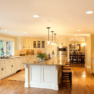 Traditional kitchen designs - Kitchen - traditional l-shaped medium tone wood floor kitchen idea in Seattle with granite countertops, recessed-panel cabinets, white cabinets, paneled appliances, an undermount sink, white backsplash, ceramic backsplash and an island