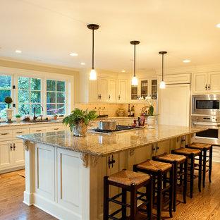 Esempio di una cucina chic di medie dimensioni con ante beige, paraspruzzi beige, elettrodomestici da incasso, paraspruzzi con piastrelle in ceramica, isola e pavimento in legno massello medio