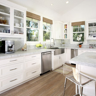 Elegant kitchen photo in San Francisco with glass-front cabinets, stainless steel appliances and a farmhouse sink
