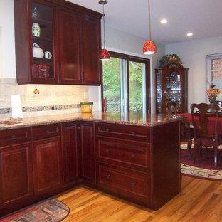 Klassische Wohnküche in L-Form mit Unterbauwaschbecken, Schrankfronten mit vertiefter Füllung, dunklen Holzschränken, Granit-Arbeitsplatte, Küchenrückwand in Beige, Rückwand aus Steinfliesen, Küchengeräten aus Edelstahl und braunem Holzboden in Cincinnati