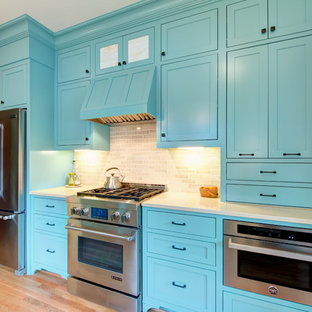 Large traditional enclosed kitchen appliance - Enclosed kitchen - large traditional galley light wood floor enclosed kitchen idea in Portland with a farmhouse sink, shaker cabinets, blue cabinets, quartz countertops, beige backsplash, subway tile backsplash, stainless steel appliances and no island