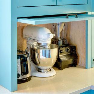 ポートランドの大きいトラディショナルスタイルのおしゃれなキッチン (エプロンフロントシンク、シェーカースタイル扉のキャビネット、青いキャビネット、クオーツストーンカウンター、ベージュキッチンパネル、サブウェイタイルのキッチンパネル、シルバーの調理設備の、淡色無垢フローリング、アイランドなし) の写真