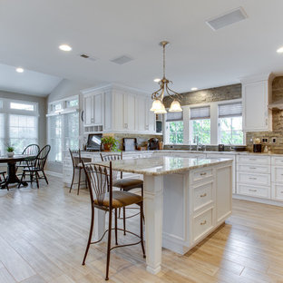 Inspiration for a large traditional u-shaped kitchen in DC Metro with an undermount sink, recessed-panel cabinets, granite benchtops, stone tile splashback, stainless steel appliances and multiple islands.