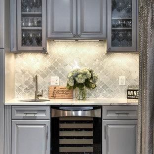 ワシントンD.C.のトラディショナルスタイルのおしゃれなアイランドキッチン (アンダーカウンターシンク、レイズドパネル扉のキャビネット、グレーのキャビネット、クオーツストーンカウンター、シルバーの調理設備の、濃色無垢フローリング) の写真