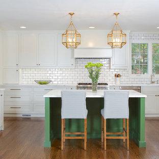 アトランタの中くらいのトラディショナルスタイルのおしゃれなアイランドキッチン (シェーカースタイル扉のキャビネット、白いキャビネット、白いキッチンパネル、サブウェイタイルのキッチンパネル、シルバーの調理設備、無垢フローリング、オレンジの床) の写真
