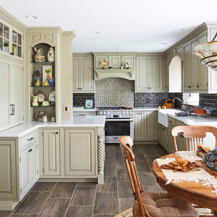 Traditional eat-in kitchen pictures - Example of a classic porcelain floor and brown floor eat-in kitchen design in Other with a farmhouse sink, quartz countertops, stainless steel appliances, raised-panel cabinets, green cabinets, gray backsplash and subway tile backsplash