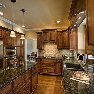 Geschlossene Klassische Küche in U-Form mit Küchengeräten aus Edelstahl, Doppelwaschbecken, profilierten Schrankfronten, dunklen Holzschränken, Granit-Arbeitsplatte, Küchenrückwand in Beige und Rückwand aus Travertin in Dallas