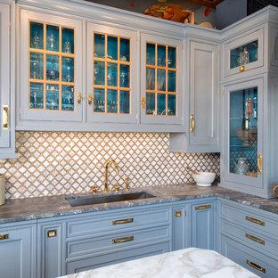 ニューヨークのトラディショナルスタイルのおしゃれなアイランドキッチン (アンダーカウンターシンク、落し込みパネル扉のキャビネット、青いキャビネット、石タイルのキッチンパネル、シルバーの調理設備) の写真
