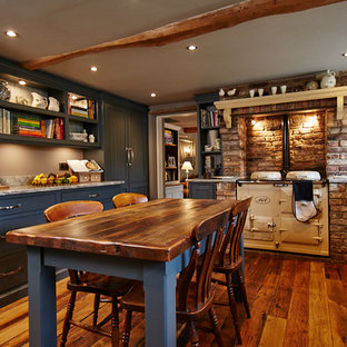 This is an example of a medium sized traditional kitchen/diner in Other with recessed-panel cabinets, blue cabinets, brick splashback, medium hardwood flooring, no island, brown floors and grey worktops.