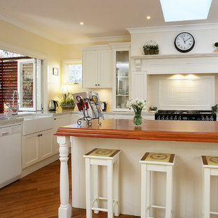 Large traditional eat-in kitchen ideas - Inspiration for a large timeless u-shaped medium tone wood floor eat-in kitchen remodel in Sydney with a farmhouse sink, wood countertops, shaker cabinets, white cabinets, white backsplash, ceramic backsplash, white appliances and an island