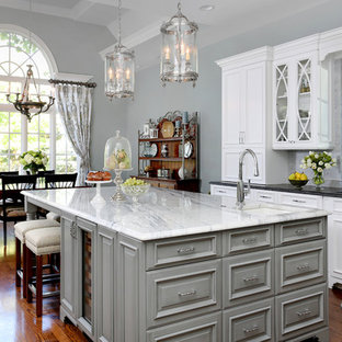 Large traditional eat-in kitchen ideas - Large elegant l-shaped dark wood floor eat-in kitchen photo in Chicago with an undermount sink, raised-panel cabinets, white cabinets, granite countertops, gray backsplash, stone tile backsplash, stainless steel appliances and an island