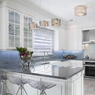 Geschlossene, Mittelgroße Klassische Küche in U-Form mit Landhausspüle, profilierten Schrankfronten, weißen Schränken, Arbeitsplatte aus Terrazzo, Küchenrückwand in Grau, Glasrückwand, Küchengeräten aus Edelstahl, Porzellan-Bodenfliesen, Halbinsel und grauem Boden in Miami