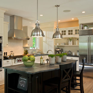 Mid-sized traditional kitchen designs - Mid-sized elegant l-shaped light wood floor kitchen photo in Boston with a farmhouse sink, subway tile backsplash, stainless steel appliances, shaker cabinets, white cabinets, solid surface countertops, white backsplash and an island
