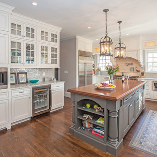 Inspiration for a mid-sized timeless u-shaped dark wood floor and brown floor eat-in kitchen remodel in Boston with a farmhouse sink, beaded inset cabinets, white cabinets, wood countertops, beige backsplash, cement tile backsplash, stainless steel appliances and an island