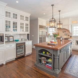 Exempel på ett mellanstort klassiskt kök, med en rustik diskho, luckor med profilerade fronter, vita skåp, träbänkskiva, beige stänkskydd, stänkskydd i cementkakel, rostfria vitvaror, mörkt trägolv, en köksö och brunt golv