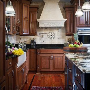 Immagine di una cucina tradizionale di medie dimensioni con lavello stile country, top in granito, ante con bugna sagomata, ante in legno scuro, paraspruzzi bianco, paraspruzzi in gres porcellanato, elettrodomestici in acciaio inossidabile, pavimento in legno massello medio e top nero
