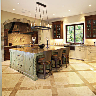Example of a large mountain style u-shaped travertine floor and beige floor enclosed kitchen design in Miami with mosaic tile backsplash, a farmhouse sink, beaded inset cabinets, white cabinets, granite countertops, paneled appliances and an island