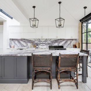 This is an example of a transitional galley kitchen in Sydney with a farmhouse sink, shaker cabinets, white cabinets, grey splashback, stone slab splashback, black appliances, with island, beige floor, grey benchtop, timber and vaulted.
