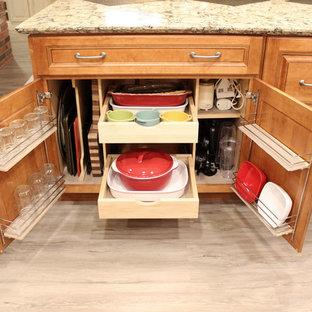 クリーブランドの中くらいのトランジショナルスタイルのおしゃれなキッチン (アンダーカウンターシンク、レイズドパネル扉のキャビネット、中間色木目調キャビネット、クオーツストーンカウンター、ベージュキッチンパネル、ライムストーンのキッチンパネル、シルバーの調理設備、クッションフロア、グレーの床、ベージュのキッチンカウンター) の写真