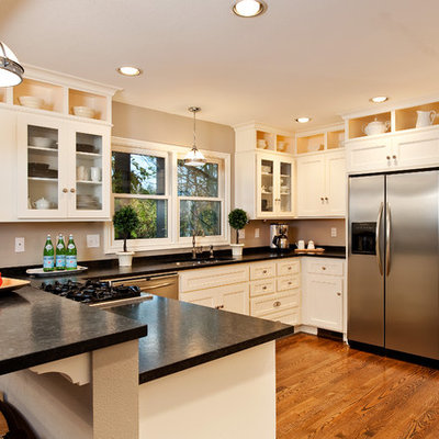 Kitchen - traditional u-shaped medium tone wood floor kitchen idea in Portland with stainless steel appliances, white cabinets, granite countertops, an undermount sink and recessed-panel cabinets