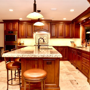 Design ideas for a large traditional u-shaped eat-in kitchen in Chicago with a double-bowl sink, raised-panel cabinets, medium wood cabinets, granite benchtops, beige splashback, travertine splashback, black appliances, travertine floors, with island, beige floor and beige benchtop.