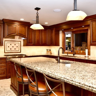 This is an example of a large traditional u-shaped eat-in kitchen in Chicago with a double-bowl sink, raised-panel cabinets, medium wood cabinets, granite benchtops, beige splashback, travertine splashback, black appliances, travertine floors, with island, beige floor and beige benchtop.