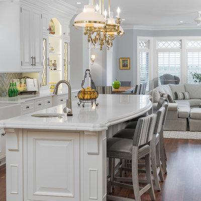 Huge elegant u-shaped medium tone wood floor and brown floor open concept kitchen photo in Newark with an island, raised-panel cabinets, white cabinets, quartz countertops, gray backsplash, ceramic backsplash, white countertops, a farmhouse sink and paneled appliances