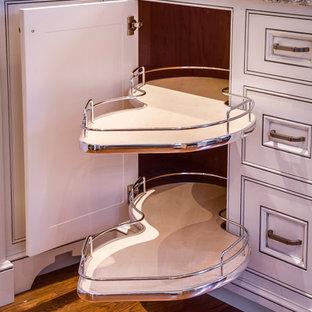 Mittelgroße Klassische Wohnküche in U-Form mit Unterbauwaschbecken, Kassettenfronten, weißen Schränken, Granit-Arbeitsplatte, Küchengeräten aus Edelstahl, dunklem Holzboden und braunem Boden in Toronto