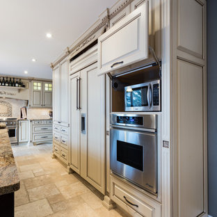 Design ideas for a large traditional kitchen in Other with raised-panel cabinets, beige cabinets, granite benchtops, beige splashback, stone tile splashback, panelled appliances and travertine floors.