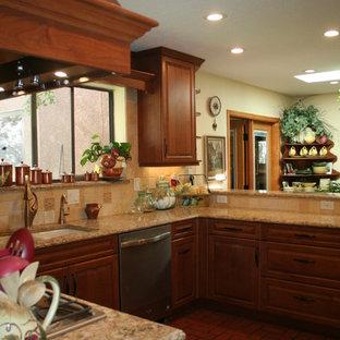 アルバカーキの中サイズのトラディショナルスタイルのおしゃれなキッチン (アンダーカウンターシンク、レイズドパネル扉のキャビネット、中間色木目調キャビネット、石タイルのキッチンパネル、レンガの床、人工大理石カウンター、ベージュキッチンパネル、パネルと同色の調理設備、赤い床) の写真