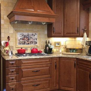 アルバカーキの中くらいのトラディショナルスタイルのおしゃれなキッチン (レイズドパネル扉のキャビネット、中間色木目調キャビネット、人工大理石カウンター、石タイルのキッチンパネル、レンガの床、アンダーカウンターシンク、ベージュキッチンパネル、パネルと同色の調理設備、赤い床) の写真