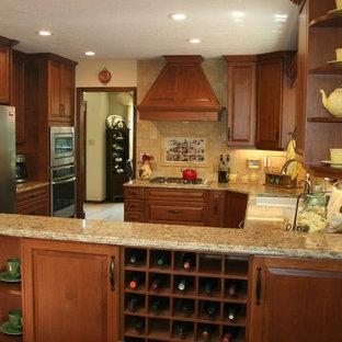アルバカーキの中サイズのトラディショナルスタイルのおしゃれなキッチン (アンダーカウンターシンク、レイズドパネル扉のキャビネット、中間色木目調キャビネット、石タイルのキッチンパネル、レンガの床、赤い床、人工大理石カウンター、ベージュキッチンパネル、パネルと同色の調理設備) の写真