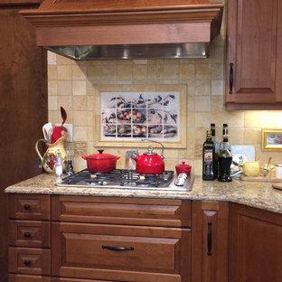 アルバカーキの中サイズのトラディショナルスタイルのおしゃれなキッチン (アンダーカウンターシンク、レイズドパネル扉のキャビネット、中間色木目調キャビネット、人工大理石カウンター、ベージュキッチンパネル、石タイルのキッチンパネル、パネルと同色の調理設備、レンガの床、赤い床) の写真