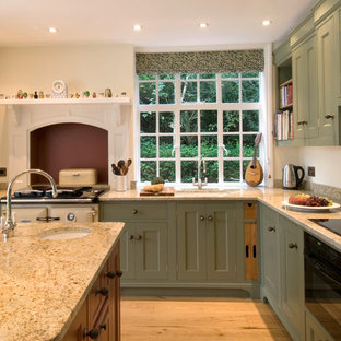 Traditional eat-in kitchen pictures - Inspiration for a timeless light wood floor eat-in kitchen remodel in Hampshire with an undermount sink, beaded inset cabinets, green cabinets, granite countertops, glass sheet backsplash and black appliances