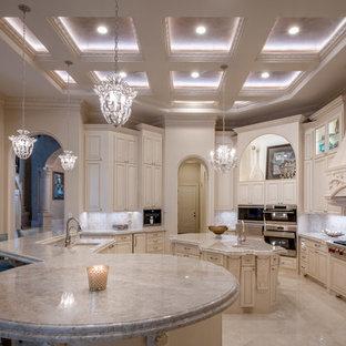 Inspiration för mycket stora medelhavsstil beige kök, med en undermonterad diskho, luckor med upphöjd panel, beige skåp, granitbänkskiva, beige stänkskydd, stänkskydd i keramik, rostfria vitvaror, klinkergolv i porslin, flera köksöar och beiget golv