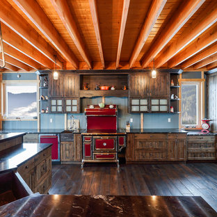 Inspiration for a country kitchen in Vancouver with an undermount sink, louvered cabinets, dark wood cabinets, coloured appliances, dark hardwood floors, with island, brown floor and black benchtop.