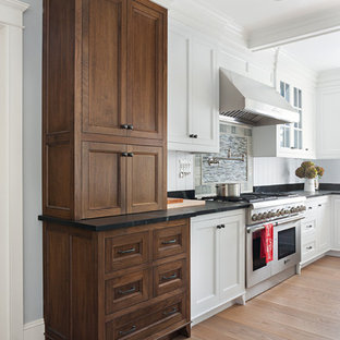 Design ideas for a classic l-shaped enclosed kitchen in Boston with a submerged sink, beaded cabinets, dark wood cabinets, soapstone worktops, stainless steel appliances, light hardwood flooring, an island, black splashback and stone slab splashback.
