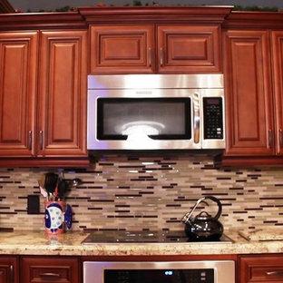 Idee per una cucina chic di medie dimensioni con lavello sottopiano, ante con bugna sagomata, ante in legno scuro, top in granito, paraspruzzi multicolore, paraspruzzi con piastrelle a mosaico, elettrodomestici da incasso, pavimento in gres porcellanato e penisola