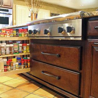 オースティンの中くらいのトラディショナルスタイルのおしゃれなキッチン (アンダーカウンターシンク、レイズドパネル扉のキャビネット、濃色木目調キャビネット、御影石カウンター、ベージュキッチンパネル、石タイルのキッチンパネル、シルバーの調理設備、テラコッタタイルの床、アイランドなし) の写真