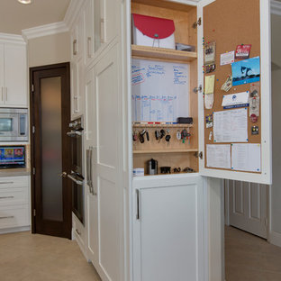 Photo of a medium sized classic u-shaped kitchen pantry in San Diego with a submerged sink, recessed-panel cabinets, white cabinets, quartz worktops, grey splashback, ceramic splashback, stainless steel appliances, porcelain flooring and an island.